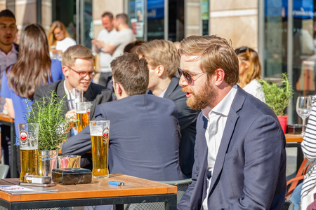London, UK - May 10, 2017 - A young businessman at a outdoor bar in Canary Wharf packed with people drinking on a sunny day