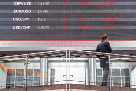 London, UK - May 15, 2017 - Stock market data displayed on a outdoor screen in Canary Wharf with a man standing in front of it