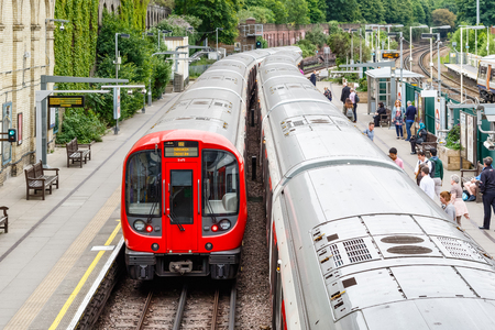 London, UK - May 23, 2017 - West Brompton underground station platforms, with commuters boarding the train Redakční