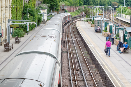 London, UK - May 23, 2017 - West Brompton underground station platforms, with southbound train leaving from platform