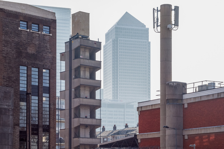London, UK - May 24, 2017 - Skyscrapers in Canary Wharf seen through old industry buildings in Poplar, East London