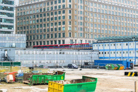 London, UK - May 24, 2017 - Construction site of Crossrail Place in Canary Wharf with DLR train passing in the background