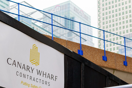 London, UK - May 24, 2017 - New development construction site in Canary Wharf with elevated DLR rail track and Citigroup Center building in the background