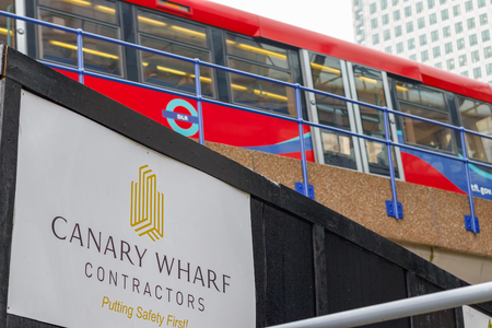 London, UK - May 24, 2017 - New development construction site in Canary Wharf with DLR train passing in the background