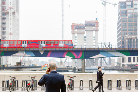 London, UK - May 24, 2017 - A businessman talking on the mobile while facing Middle Dock in Canary Wharf with DLR trains passing and building site of Newfoundland, a new residential development, in the background