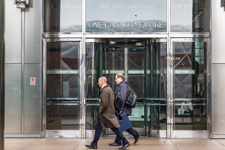 London, UK - May 24, 2017 - Entrance of One Canada Square, a skyscraper in Canary Wharf, with people walking in motion in front of the doors Redakční