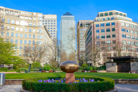 'Cosmic Stone' by Do Vassilakis-Koning in a peaceful garden at Westferry Circus in Canary Wharf with skyscrapers in the background Фото со стока