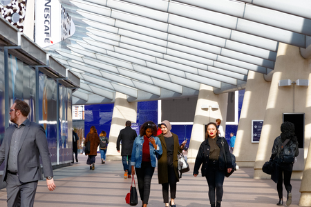 London, UK - June 25, 2017 - People walking on a passageway in Peninsula Square leading to The O2 or North Greenwich station