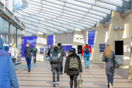 London, UK - June 25, 2018 - People walking on a passageway in Peninsula Square leading to The O2 or North Greenwich station