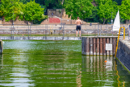Back view of a topless young man standing on swimming docks at Shadwell Basin in London Reklamní fotografie