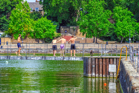 Back view of a group of topless young men standing on swimming docks at Shadwell Basin in London