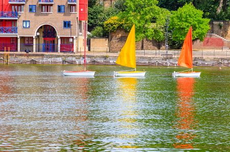 Three sailing dinghies in different colours float on Shadwell Basin in London