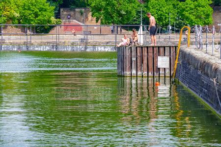 London, UK - June 21, 2017 - Three shirtless young men sunbathe on the swimming dock at Shadwell Basin Redactioneel