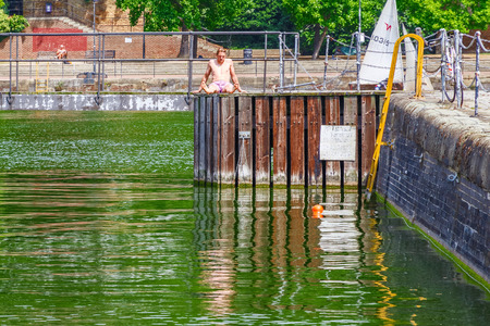 London, UK - June 21, 2018 - a shirtless young men sunbathe on the swimming dock at Shadwell Basin