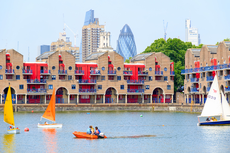 London, UK - June 21, 2017 - Shadwell Basin provides space for water sports and adventurous activities with dockside apartments and The Gherkin in the background