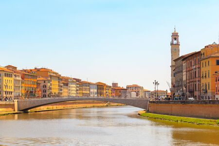Ponte di Mezzo (Mezzo Bridge) on Arno river with Pisa cityscape in the background in Tuscany, Italy
