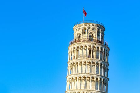 Sunset at the leaning tower of Pisa, Italy against a cloudless blue sky