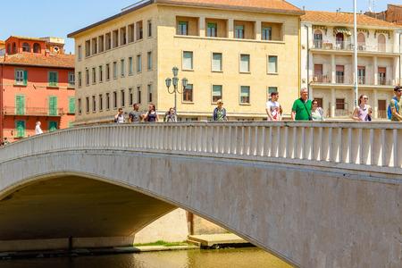 Pisa, Italy - June 26, 2019 - Tourists walk on Ponte di Mezzo (Mezzo Bridge) over river Arno