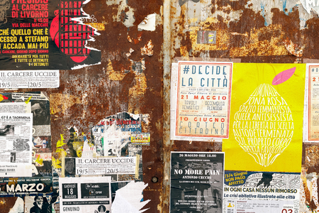 Pisa, Italy - June 26, 2019 - Rusty doors covered by torn promotional posters and stickers on a city street of Pisa