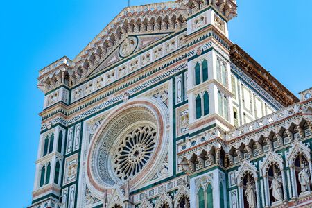Facade of the Cattedrale di Santa Maria del Fiore (Cathedral of Saint Mary of the Flower) in Florence, Italy against a cloudless sky