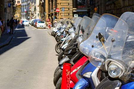 A typical street of Florence with motorcycle scooters parked in row in Italy