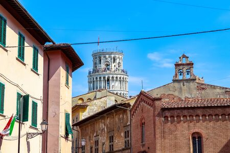 The Leaning Tower of Pisa seen amid typical local buildings against a blue cloudless sky Stockfoto