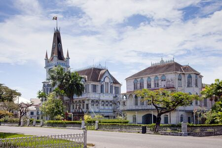 View of an old wooden fairy-tale Gothic building with spires and turrets on a clear Sunny day, the city hall of Georgetown, Guyana. World tourism, architecture.