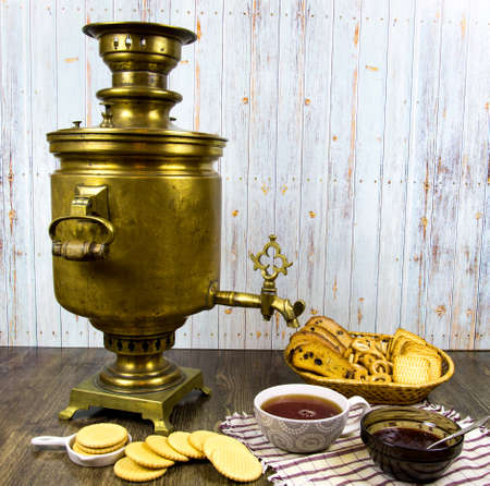 Antique copper samovar on a wooden table with a Cup of tea breadcrumbs cookies jam. Traditions of peoples, culture, cuisine.
