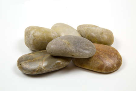 Sea semicircular polished stones of gray brown yellow color folded in a certain figure, isolated on a white background.