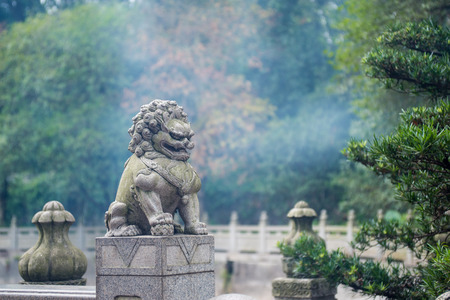 stone lion sculpture on the fence in the park photo