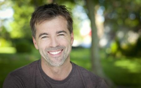 ��smiling: Hombre hermoso que sonr�e en el parque Foto de archivo