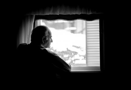 hombre preocupado: Hombre mayor solo mirando la ventana