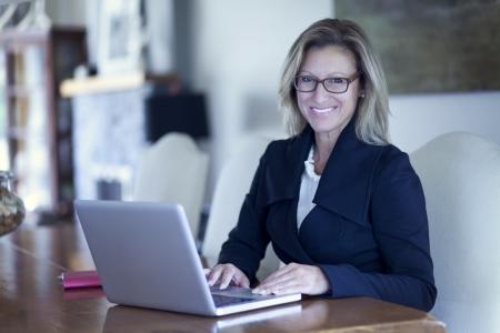 Businesswoman At Home Office Using Laptop Banco de Imagens