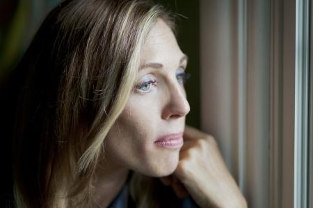 worried woman: Sad woman at the window