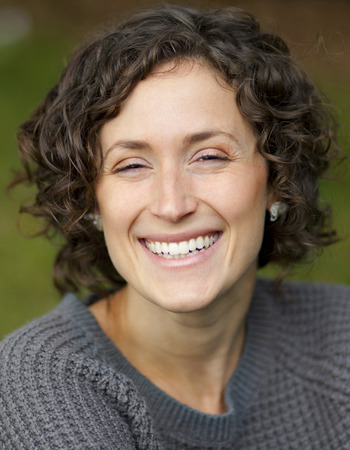 Close-up Of A Mature Woman Smiling At The Camera. She is serene and in peace.
