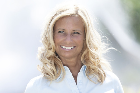 Mature blond woman smiling at the camera photo