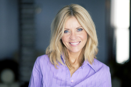 Portrait of a mature blond woman smiling at the camera