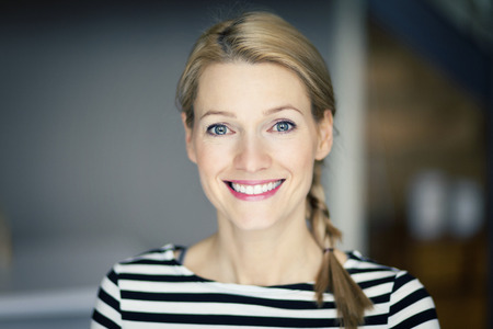 ストライプのシャツを着て笑顔の金髪女性