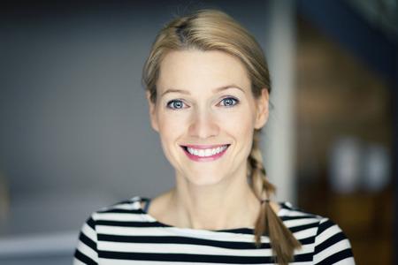 vrouwen: Glimlachende blonde vrouw, gekleed in een gestreept overhemd Stockfoto