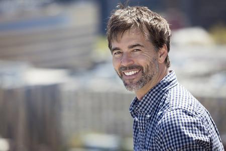 hombres maduros: Retrato de un hombre activo maduro que sonríe en una ciudad