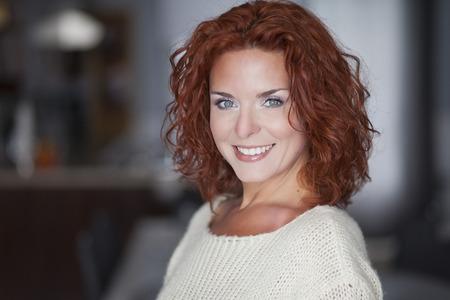 カメラに向かって笑みを浮かべて赤い女性の肖像