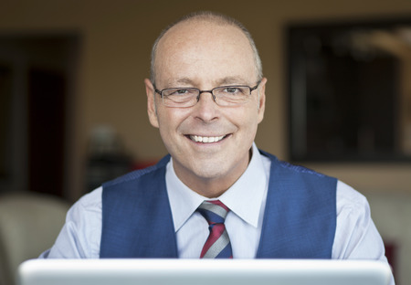 doctor money: Mature Businessman Smiling At The Camera. Hes working at home. Stock Photo