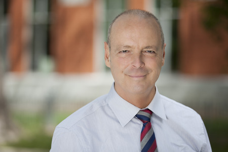 man doctor: Mature Businessman Smiling At The Camera. He is outside of the office