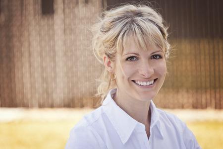 cabello rubio: Mujer bonita sonriendo a la cámara en el patio trasero
