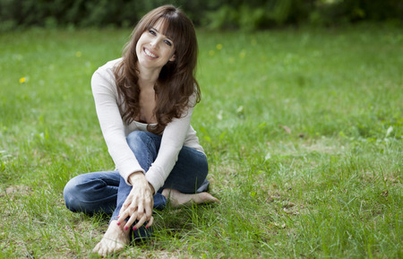 Mooie vrouw lachend op de camera zit in het park