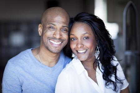 sonriente: Retrato de un par Negro sonriente a la cámara en casa