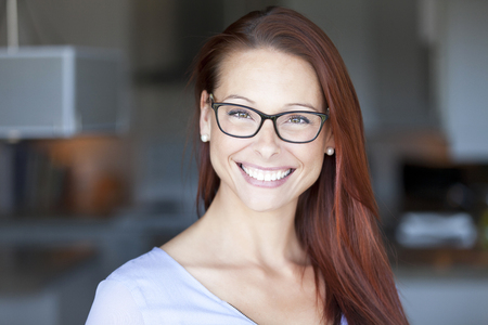 カメラを見る家で笑顔の女性。メガネ。