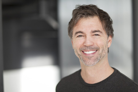ojos verdes: Retrato de un hombre maduro sonriente a la cámara. Casa