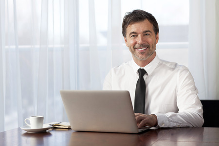 Businessman teleworking at home. On a Laptop. Smiling