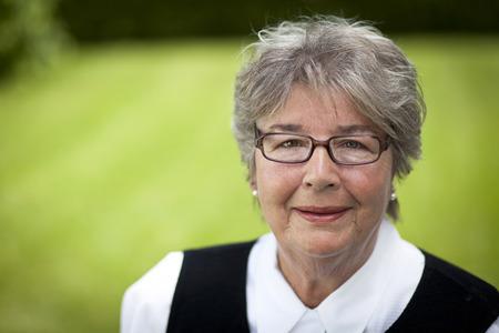 80s adult: Senior woman smiling at the camera.